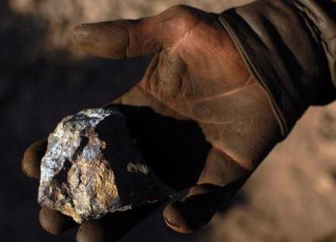 Mineral Reserves Discovery Afghanistan - a close-up photograph showing a miner's hand holding a sample of copper ore.