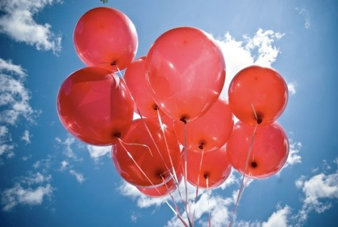 A photograph showing a bunch of Helium red party balloons on strings over a sunny blue sky background.