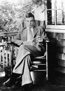 A black and white photograph showing a young Alan Turing reading in his garden.