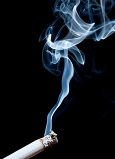 A photograph showing a lit-up cigarette with whirling smoke.