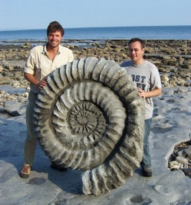 A photograph showing two very lucky fossil finders with a belemnite or ammonite giant fossil.