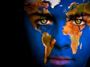 A close-up showing the face of a child painted with a World map. Mother Earth.