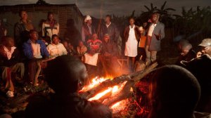 A photograph showing the members of a Ugandan community assembled at night around their village camp fire.