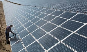 A photograph showing a technician inspecting photovoltaic panels at the largest African solar powered plant in Ghana.