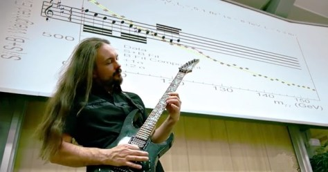 "A photograph featuring an electric guitar player and the music score of the Higgs ""sonification"" by the rock band, Traq."