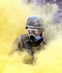 A photograph of an army soldier wearing a protective gas mask, surrounded by a cloud of noxious yellow smoke - presumably yperite mustard gas.