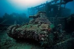 A photograph showing a submerged tank covered in sea algae and barnacles.