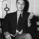 "A black and white photograph of physicist Robert Oppenheimer, pictured sitting down and smoking, with his post-war ""Bold Look"" wide short tie."