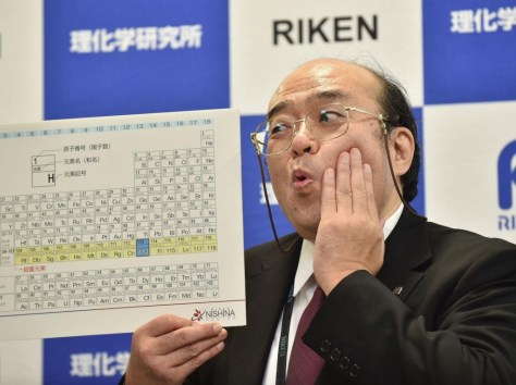 A photograph of Kosuke Morita, the leader of the Riken team, posing with a board displaying the new atomic element 113 during a press conference in Wako, Saitama prefecture on 31 December 2015.