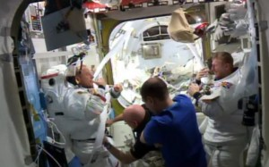 A photograph taken inside the International Space Station of the two Tims (Kopra and Peake) back safely after Peake's first spacewalk. They are being helped out of their pressure suits by American Scott Kelly and Italian Luca Parmitano.