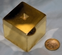 A photograph showing one of the LISA Pathfinder test masses. The shiny golden cube is compared to the size of a 1 Euro coin.