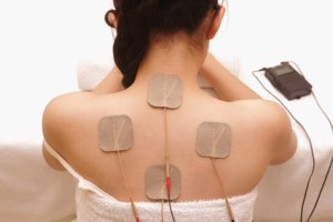 A photograph showing a woman undergoing massage by electrical-stimulation (TENs) for upper back pain.