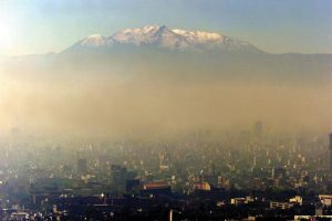 An aerial photograph showing the highly polluted skyline of Mexico City, with the heights of local strato-volcano Popocatépetl seen in the background.