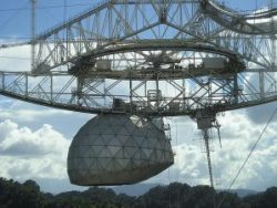 A close up photograph of the feed antenna of the Arecibo Radio Telescope, at Arecibo in Puerto Rico. The triangular platform at the top is fixed, and the azimuth arm rotates beneath it.  To the left is the Gregorian sub-reflector, and to the right is the 29-metre $ ($96-foot$ )$ long line feed tuned to 430 MHz.  Just visible at the upper right is part of the rectangular waveguide that brings the 2.5 MW 430 MHz radar transmitter's signal up to the focal region. Source: Wikipedia