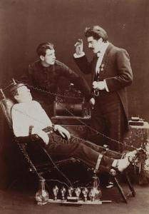 """An ancient photograph showing Dr Brodie and assistant with one of his """"patients"""" in an electrical chair."""
