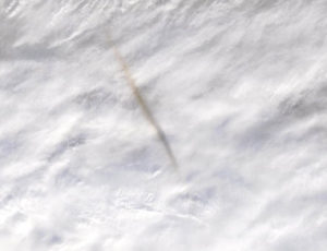 A satellite photograph showing the Bering Sea bolide dark trail on the Earth white cloud cover.