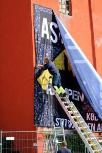 Kæmpe banner om asfalt-aktien sættes op på Maltfabrikken som huser Rampen. Foto: Rampen