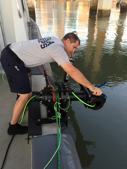 Lt. Cmdr. Jonathan French, officer in charge of navigation response team 1, homeported in Stennis, Mississippi, adjusts a side scan sonar in preparation for surveying the Port of Miami following Hurricane Irma.
