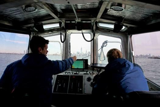 "Lt. j.g. Dylan Dylan Kosten instructing Michael Bloom on proper navigation and ""rules of the road."""