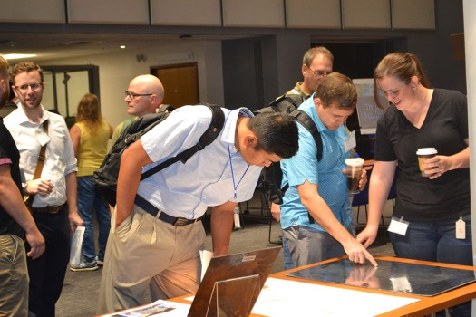 Open house attendees visit the display on historic cartographic processes.