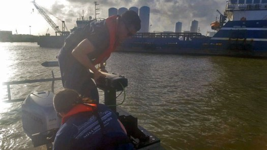 Lt. j.g. Patrick Lawler and Lt. j.g. Michelle Levano remove the side scan sonar from the water.