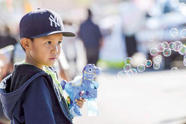Navajo Times | Krista Allen A boy uses a bubble blower to create bubbles while his family waits for the commencement of the 49th annual Western Navajo Fair parade on Saturday morning in Tónaneesdizí.
