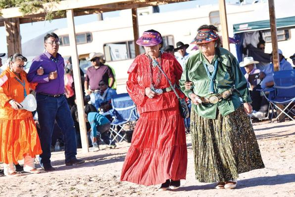 Navajo Times | Krista Allen Dressed alike, two women dance arm-in-arm in a round of two-step during the 49th annual Western Navajo Fair song and dance on Saturday evening.