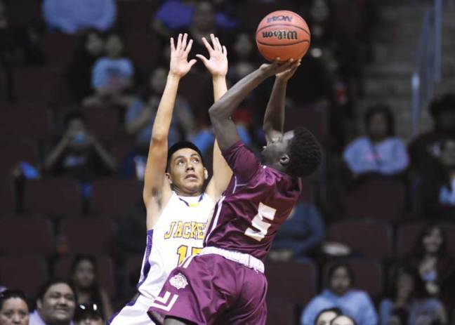Navajo Times | Donovan Quintero Winslow's Yoann Djassa (5) looks to shoot the ball over guarding Yellow Jacket Darrien Burnette on Monday at the Gila River Arena in Glendale, Ariz.