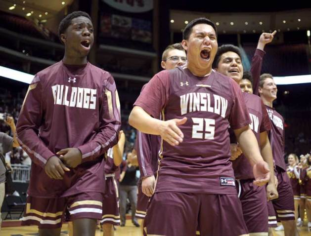 Navajo Times | Donovan Quintero Winslow Bulldog Yoann Djassa, left, and Isaac Benale (25) walk the team onto the court to receive their Arizona 3A state championship trophy Monday at the Gila River Arena in Glendale, Ariz.
