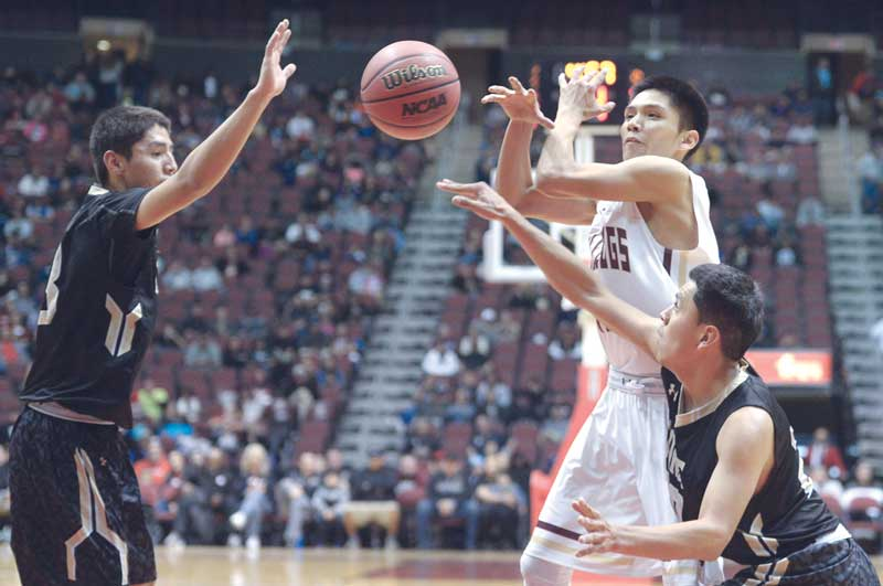 Navajo Times | Donovan Quintero Chinle Wildcat Chance Harvey, right, knocks the ball out of Winslow Bulldog Darius James' hands Friday at the Gila River Arena in Glendale, Ariz.