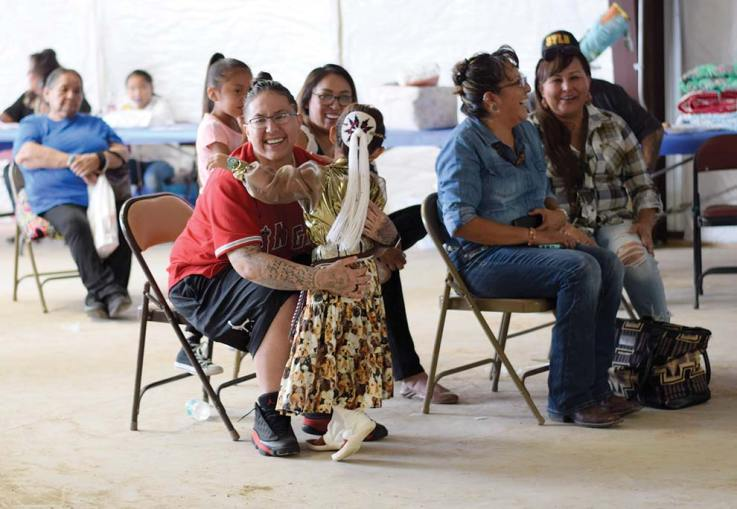 Navajo Times | Ravonelle Yazzie Destiny Lutsie, 4, runs to her auntie for a hug after performing the Navajo puppy song on stage at the baby contest on Aug. 24 at Ramah Navajo Fair and Rodeo.