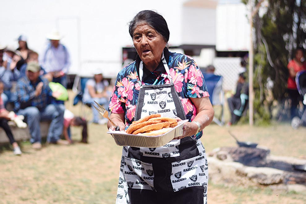 Navajo Times | Ravonelle Yazzie Ruth D. Pino carries a tray of frybread to the judges' table on Aug. 25 during the frybread contest at the Ramah Navajo Fair and Rodeo.