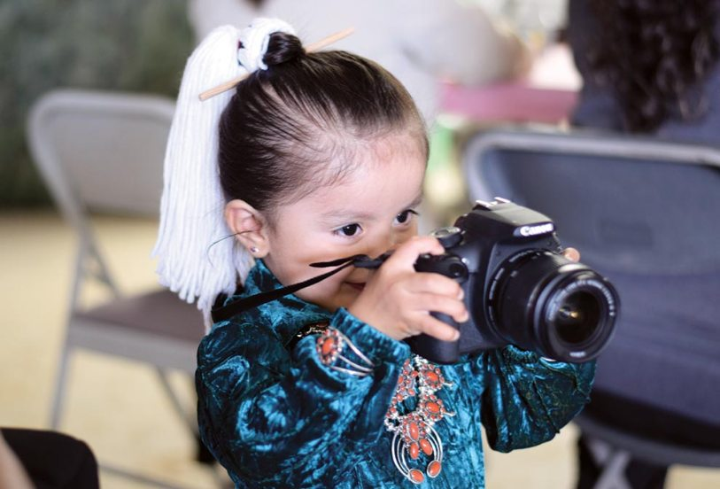 Navajo Times | Ravonelle Yazzie Reese Garcia, 2, of Tohatchi, N.M., takes a photo at the baby contest on Aug. 24 at Ramah Navajo Fair and Rodeo.
