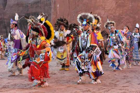Navajo Times | Rima Krisst Pow-wow dancers make their way into the arena at Red Rock Park.