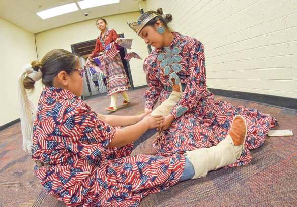 Navajo Times   Krista Allen Miss Kayenta Middle School Dawnae Yazzie helps her 9-year-old sister, D'Aaliyah, adjust the 'abaní of her kénitsaai during a Veterans Day ceremony at Monument Valley High in Tódinéeshzhee' on Nov. 12. The Yazzie sisters both wore matching patriotic outfits.