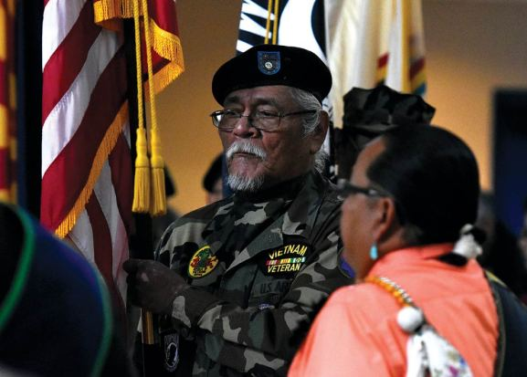 Navajo Times   Donovan Quintero A member of the Fort Defiance Veterans Organization carries the flag during the posting of the colors during a Veterans Day Gourd Dance in Fort Defiance.