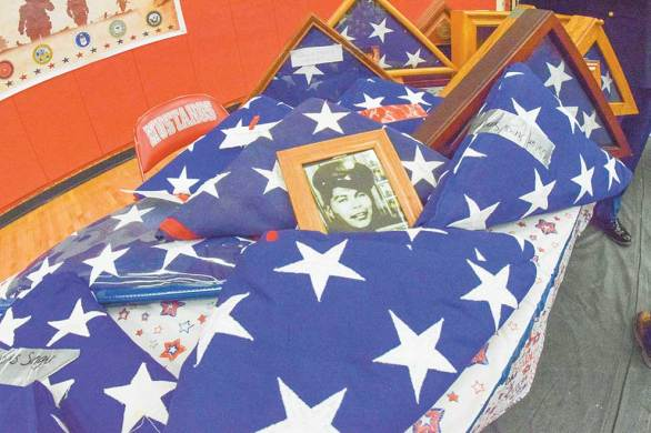 Navajo Times   Krista Allen A portrait of a man in military uniform lies against a burial flag among other Stars and Stripes during a Veterans Day ceremony at Monument Valley High in Tódinéeshzhee' on Nov. 12. Each of the flags were unfolded, refolded, and then presented back to families.