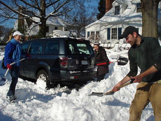 A man shoveling his neighbor's snow