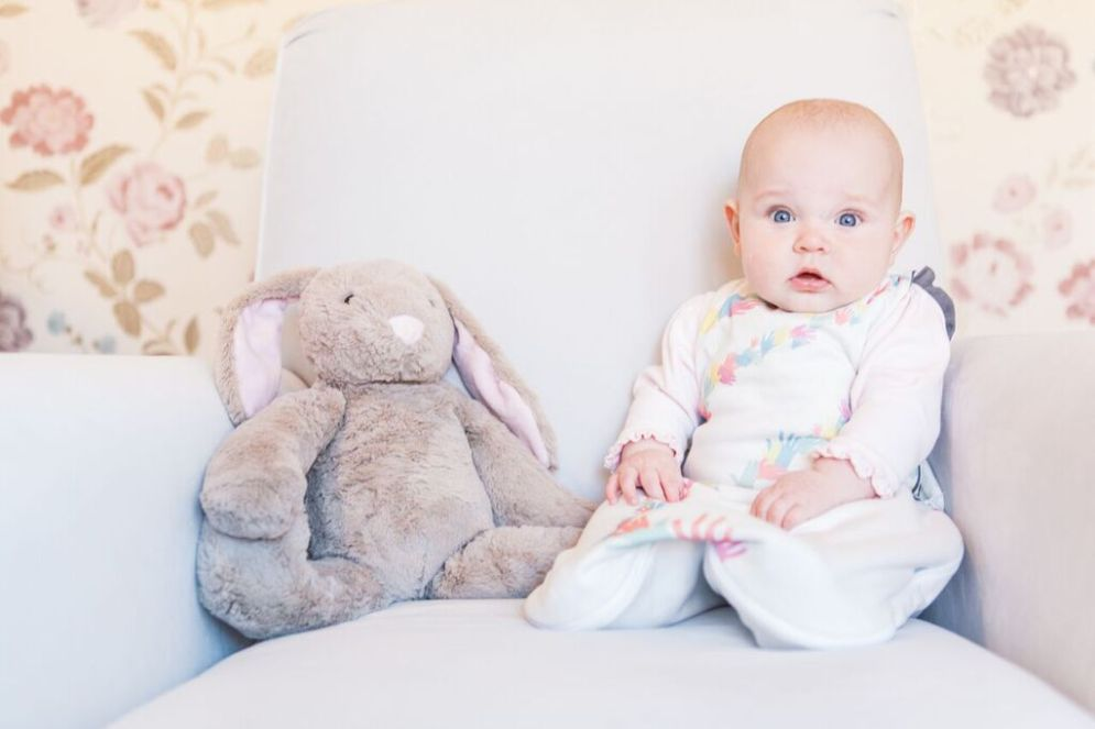 baby sitting next to stuffed toy rabbit