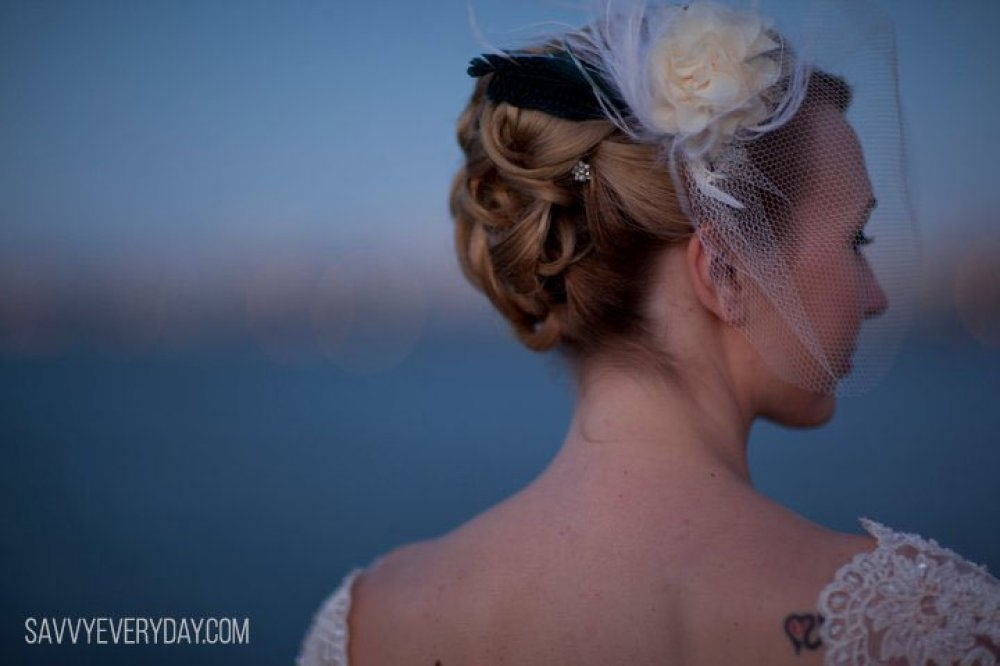 Picture of Shari in wedding dress with back to camera and head turned toward camera slightly. Tattoo on right shoulder blade.