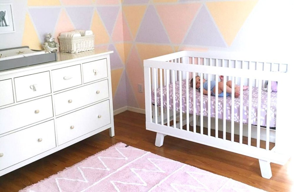 Image of a nursery room with white crib and geometric designs painted on the corner of the wall