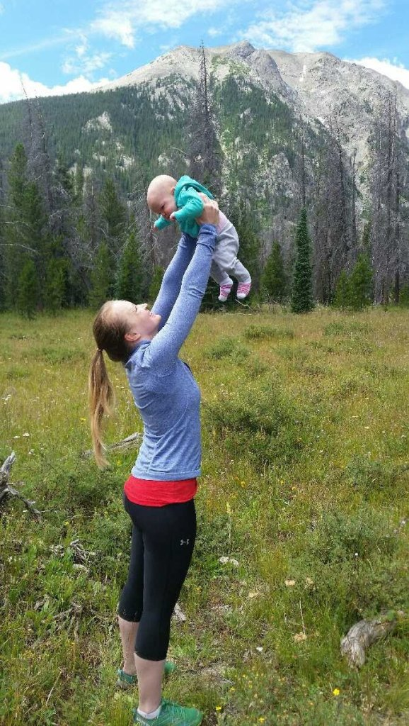 holding baby at mountains