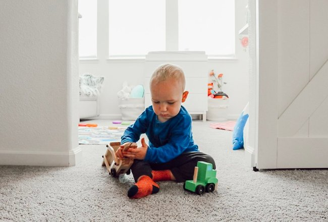 Boy playing with truck set between the shared kids room spaces