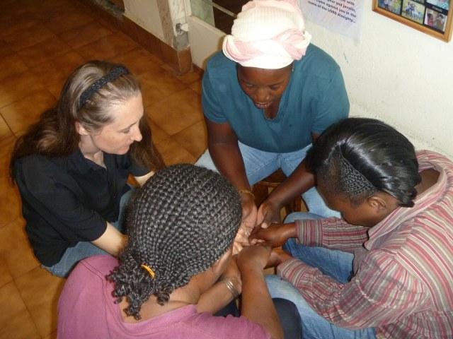 Lydia Klingforth praying with women she mentors in Kenya