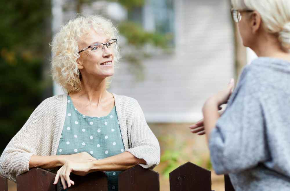 Share God's Love With Your Neighbors | Two mature female neighbours talking through fence about everyday life