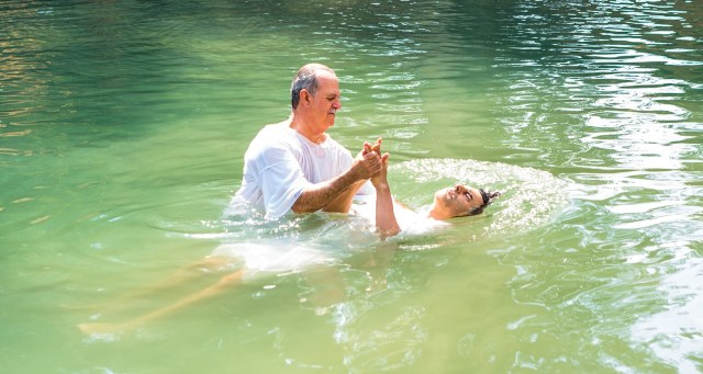 Raised to Life | Navigators World Missions | Young man being baptized in a river