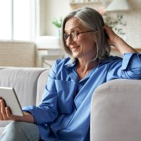 Women's Bible Study: Living for What Really Matters | Navigators Bible Study Resource | Happy 60s older mature middle aged adult woman holding digital tablet computer conference calling by social distance virtual family online chat meeting or watching video sitting on couch at home.