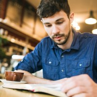 Assurance of Salvation Bible Study | Navigators Bible Study Resource | Young man reading a book at a coffee shop