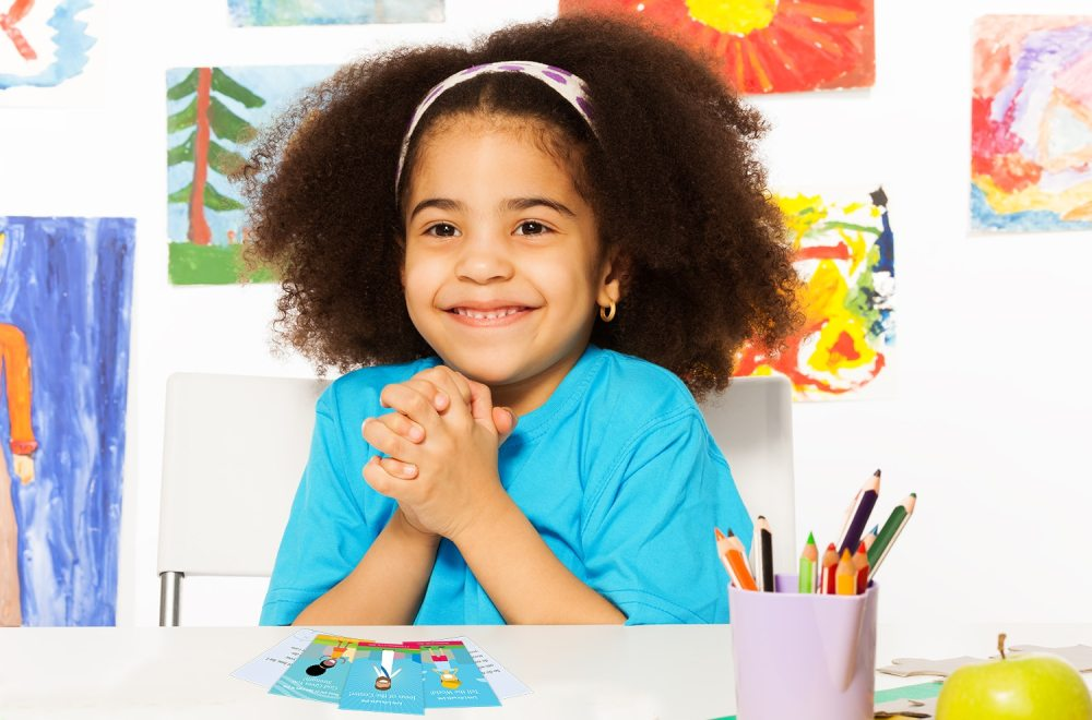 Topical Memory System for Kids | Navigators Bible Study Resource | Happy young girl holds her hands together while sitting in playroom with wall behind full of children drawings
