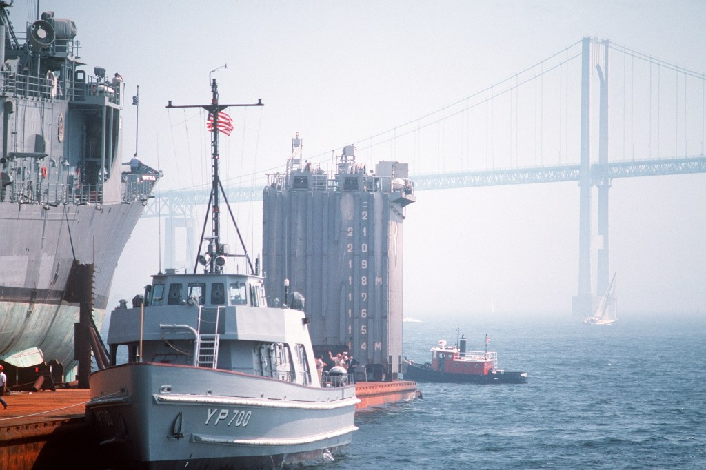Yard Patrol craft No. 700, part of the Newport Naval Education and Training Center's pocket fleet, comes alongside<i>Roberts</i>not far from the Newport Bridge.(PH2 Elliott/U.S. Navy)